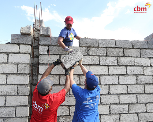 Ian, Neilesh & Brian work together to build an outside wall on one of the quad-plexes